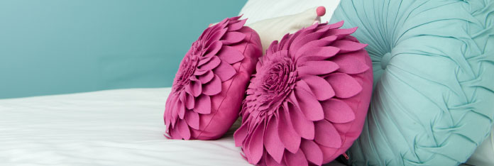 Pink and Blue Cushions on Bed